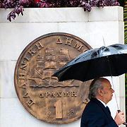 A pedestrian with an umbrella under rain passing by a plaque portraying an old drachma coin, which was replaced by the euro in 2002, outside Athens City Hall