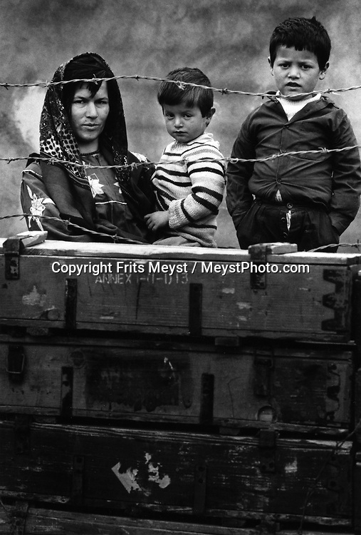 MAWAT, KURDISTAN, IRAQ, MARCH 1994. A Kurdish family stands behind their fence of recicled war material. Twenty million landmines and unexploded ordnance litter the former frontline in the Iran vs Iraq War still killing and maim ing Kurdish people on a daily basis.©Photo by Frits Meyst/NewsImages