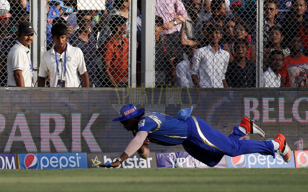Mumbai Indians player Kieron Pollard dives to stop a boundary during match 23 of the Pepsi IPL 2015 (Indian Premier League) between The Mumbai Indians and The Sunrisers Hyderabad held at the Wankhede Stadium in Mumbai India on the 25th April 2015.<br /> <br /> Photo by:  Vipin Pawar / SPORTZPICS / IPL