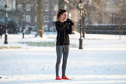 © Licensed to London News Pictures. 28/02/2018. London, UK. A jogger stops to take a photograph of snow in Green Park on her phone after heavy overnight snowfall as the 'Beast from the East brings freezing Siberian air to the UK. Photo credit: Rob Pinney/LNP