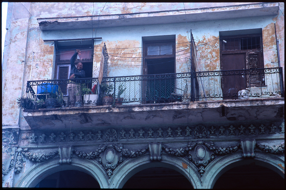 Old man on rustic balcony, Havana, Cuba