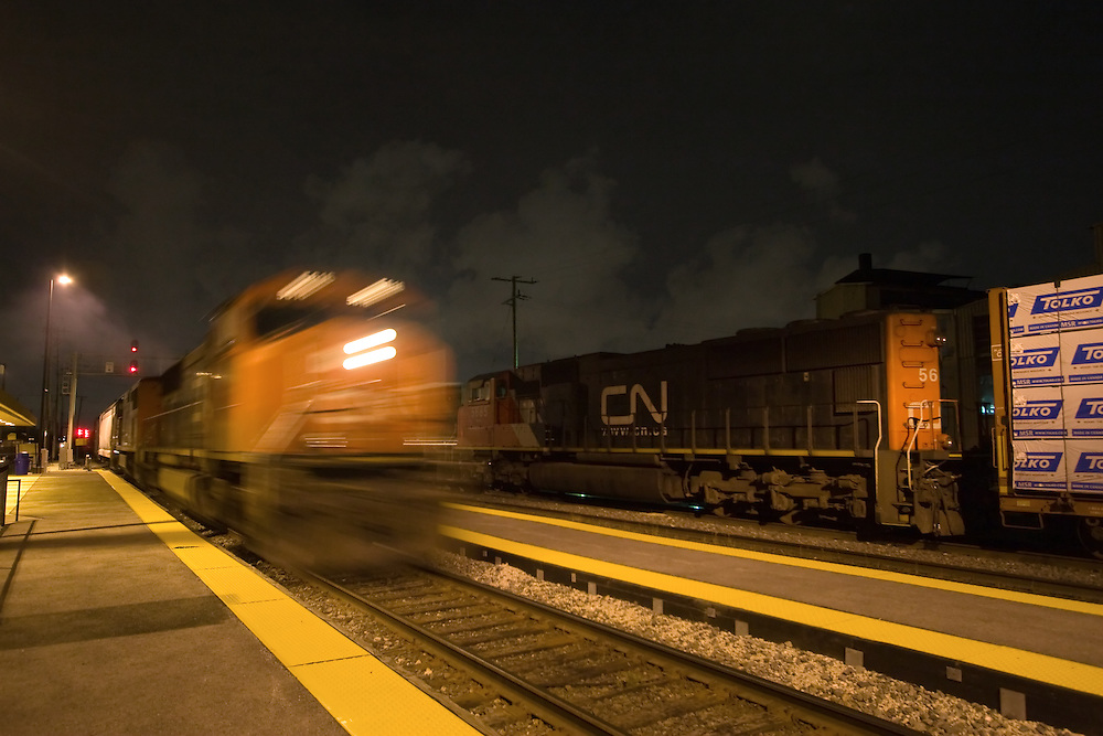 Two Canadian National freight trains meet at the Franklin Park, IL Metra commuter depot late at night.