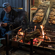 """BUDAPEST, HUNGARY - DECEMBER 07:  A stall holder prepares some smoked food   at the """"Basilica"""" Christmas fair on December 7, 2017 in Budapest, Hungary. The traditional Christmas market and lights will stay until 31st December 2017."""
