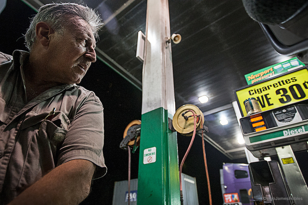 "Joe keeps a watchful eye on the pump as he fuels up for the next day's delivery. ""They don't care that people are going homeless, losing their cars and trucks and houses and having to have to struggle for food and sell things just to buy a tank full of gas,"" Joe said. ""Now they got everybody by the short hairs."""