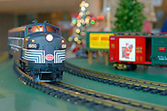 Dec. 26, 2012 - Garden City, New York, U.S. - The Long Island Garden Railway Society large-scale model train display is a festive winter holiday attraction in the vast 3-floor atrium of Cradle of Aviation museum, until shortly after New Years Day 2013. This G-scale New York Central train passes by colorful train cars as it goes along curve in the tracks. LIGRS shares the knowledge, fun, and camaraderie of large-scale railroading both indoors and in the garden, and is family oriented.
