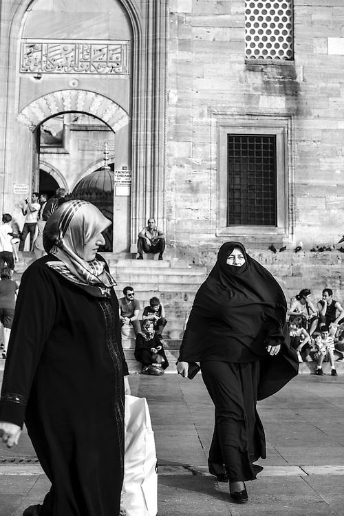 Women wearing muslim çarsaf outside New Mosque in Istanbul.