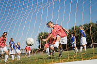 Girl (13-17) scoring with soccer ball