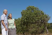 Senior couple by fruit tree smiling