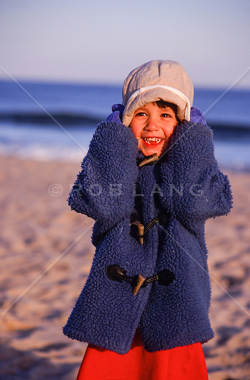 little girl holding her hat and laughing on the beach in East Hampton, NY