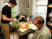 """November 7 2010 - Nat Jackson(left), Chris Knighton(center) and Rich Navan(right) prepare food, at a house in Cambridge, for a Food Not Bombs meal on Sunday in Central Square. All three volunteer with the organization which prepares vegan meals and offers them free to anyone. """"I like cooking vegan. I like the challenge,"""" Navan said. Photo by Lathan Goumas."""