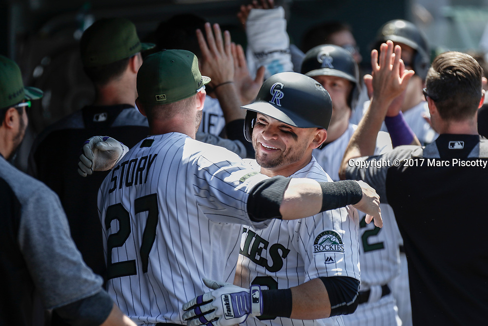 SHOT 5/28/17 1:12:28 PM - The Colorado Rockies Gerardo Parra #8 celebrates with teammates in the dugout after hitting a three-run homer against the St. Louis Cardinals during their regular season MLB game at Coors Field in Denver, Co. The Rockies won the game 8-4. (Photo by Marc Piscotty / © 2017)