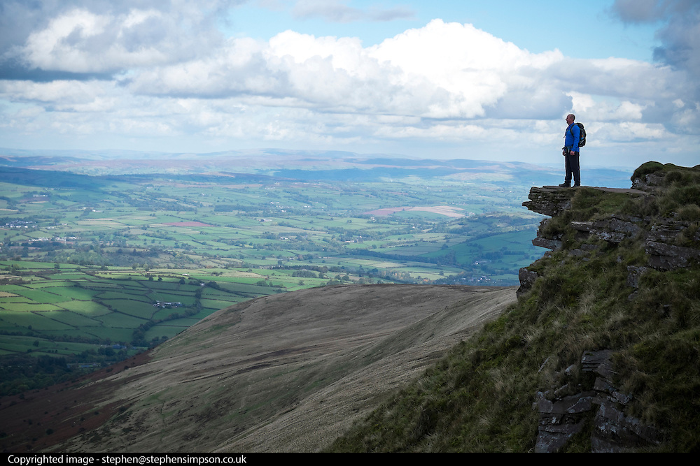 © Licensed to London News Pictures. 15/10/2016. Brecon Beacons, UK. A man pauses to take in the view.  Clouds over walkers in showery weather on Fan Y Big in the `Brecon Beacons National Park. Photo credit : Stephen Simpson/LNP