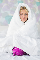 Portrait of young woman suffering from fever while wrapped in quilt in bed