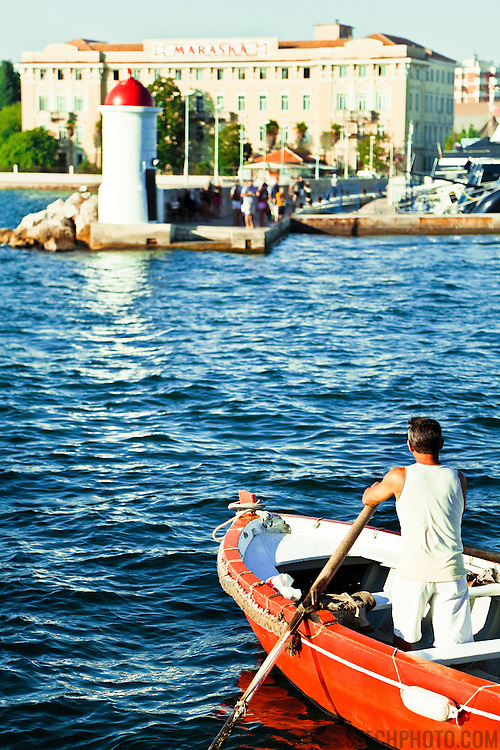 A traditional Barkarjoli (boatman) crossing the harbor in Zadar, Croatia, to pick-up a new boatload passagers destined for the old city.