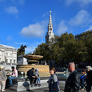 Tourists enjoy sightseers Autumn and Sunshine in Trafalgar Square, London, UK 24 October 2018