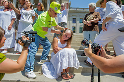 """Paula Swearengin gets her head shaved by the late Larry Gibson, founder of the Keeper of the Mountains Foundation. On Memorial Day 2012, Swearengin and Gibson joined more than a dozen women (and a few men) on the steps of the West Virginia State Capitol in Charleston to have their heads shaved to protest mountaintop-removal mining. The shaving of their heads was symbolic of the mountains that have been stripped of all of the living things on them. It was also symbolic of the many people who are sick or dying as the result of Mountaintop Removal. Mountaintop Removal is a method of surface mining that literally removes the tops of mountains to get to the coal seams beneath. It is the most profitable mining technique available because it is performed quickly, cheaply and comes with hefty economic benefits for the mining companies, most of which are located out of state. It is the most profitable mining technique available because it is performed quickly, cheaply and comes with hefty economic benefits for the mining companies, most of which are located out of state. Many argue that they have brought wage-paying jobs and modern amenities to Appalachia, but others say they have only demolished an estimated 1.4 million acres of forested hills, buried an estimated 2,000 miles of streams, poisoned drinking water, and wiped whole towns from the map. """"Watch out, King Coal,"""" Swearengin said, """"because here come the Queens of Appalachia."""" © Ami Vitale"""