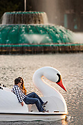 A couple paddle a Swan boat around Lake Eola Park past the Linton E. Allen Memorial Fountain in Orlando, Florida. Lake Eola Park is located in the heart of Downtown Orlando and home to the Walt Disney Amphitheater.