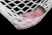 A newborn relaxes in a woolly white hammock.