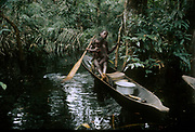 Africa, Democratic Republic of the Congo, Ngiri River islands area, Libinza tribe, girl with baby learning to paddle in canoe in swamp forest.