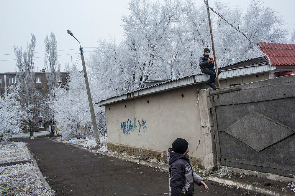 A boy sits on top of a roof after climbing the wall while his friend watches on Saturday, December 12, 2015 in Zolote, Ukraine.