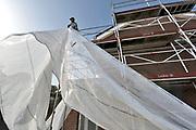 Nederland, Wijchen, 16-10-2017 Renovatie sociale huurwoningen van woningcorporatie Talis in de wijken Heilige Stoel, Homberg en Kraayenberg. Bouwvakkers zijn de energieverspillende gevels van de PeGe-woningen aan het vervangen. Ook de daken, muren en vloeren worden geisoleerd en toiletten en douche vernieuwd. Een steigerbouwer trekt een stuk doek langs een steiger om deze af te schermen.Foto: Flip Franssen