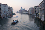Early morning transport of goods on Venice's Grand Canal seen from Ponte Accademia.