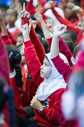 A young muslim girl with her hand up  in an assembly, junior school