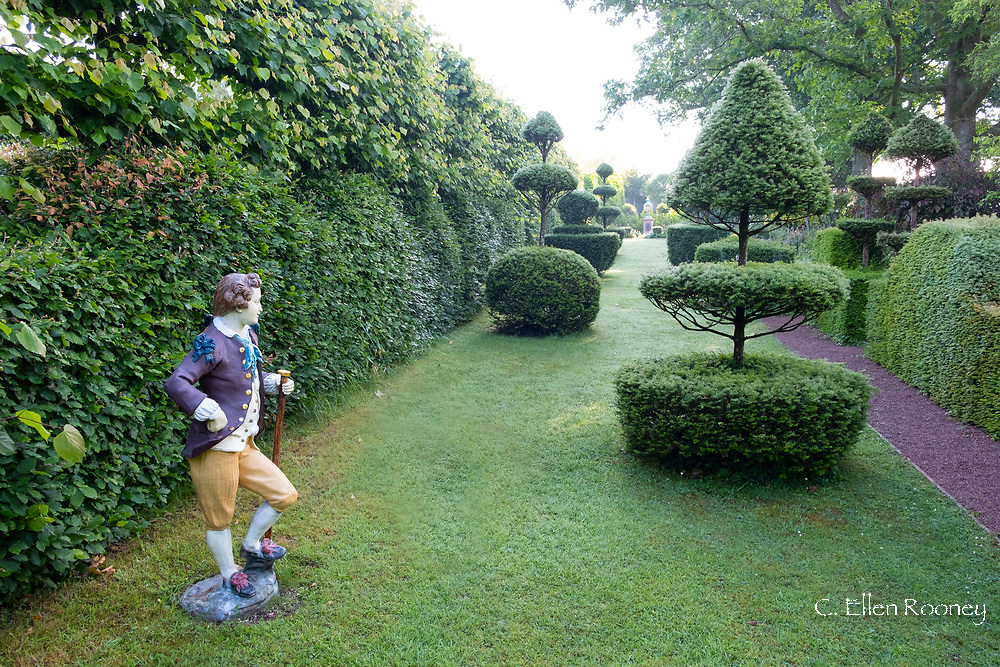 Taxus Baccata, elaborate of yew topiary along and a statue an Elizabethan gentleman in the Elizabeth Tudor Walk at the Laskett Gardens, Much Birch, Herefordshire, UK