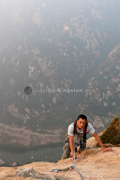 Rock climber scales a cliff in the White River gorge near Beijing, China (Model Released, Sean Ouyang).