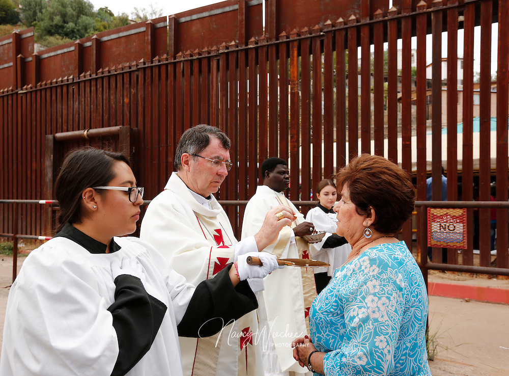 Archbishop Christophe Pierre, apostolic nuncio to the United States, gives Communion during Mass at the international border in Nogales, Arizona, Oct. 23. Dioceses Without Borders, an effort of the dioceses of Nogales, Tucson and Phoenix, organized the liturgy celebrated on both sides of the U.S.-Mexico border. (CNS photo/Nancy Wiechec)