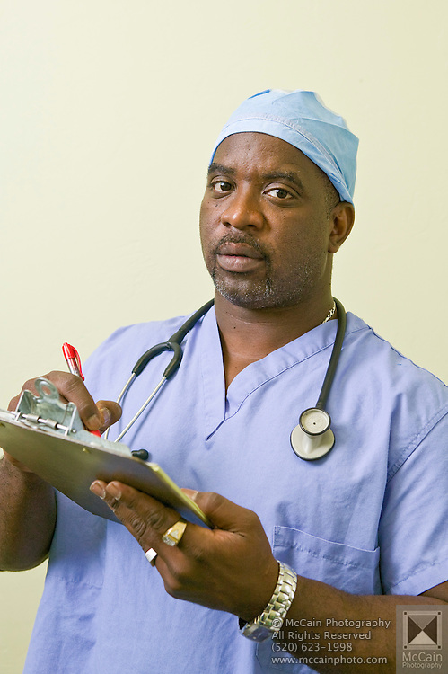 Portrait from the chest up facing camera of a male doctor looking serious wearing blue scrubs with a pen and clipboard in hands and a stethoscope around his neck, Tucson, Arizona..Media Usage:.Subject photograph(s) are copyrighted Edward McCain. All rights are reserved except those specifically granted by McCain Photography in writing...McCain Photography.211 S 4th Avenue.Tucson, AZ 85701-2103.(520) 623-1998.mobile: (520) 990-0999.fax: (520) 623-1190.http://www.mccainphoto.com.edward@mccainphoto.com