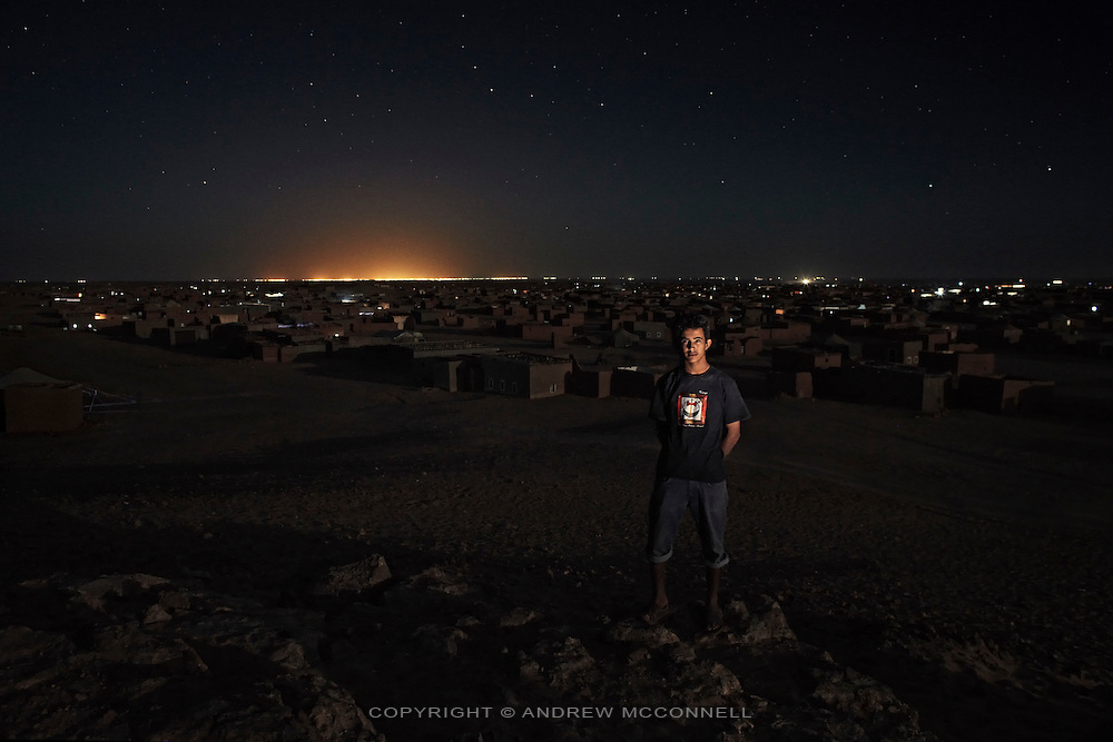 Azmah Laulad, 18, in Auserd refugee camp, Algeria, with the lights of Tindouf in the background...I've grown up in Auserd but I don't like it. When I was ten we were travelling in the desert and the truck broke down. We were stuck there for six days and had to drink water from the radiator. There was a pregnant woman with us and everyone thought she would lose the baby but it was lucky a car came along and we fixed the truck. Sometimes now I go into the desert with my friends to sleep, it's comfortable. I want to study in Spain, I've been there five times. I stay with a family in Madrid. They have very good houses there made of cement. The weather is good and the food and I have many friends but now I am too old to go back [with the Vacations in Peace program]. ..Now I'm making bricks and soon me and my brother will build a shop. We will sell mobile phones because there are not enough phone shops here. It's a tragedy here, people need to go back [to Western Sahara]. If we can get our independence peacefully it's better but if we have to we should go to war. I'm deprived of getting a job, my freedom, everything. It's God's will. If there is a war I will join the military.