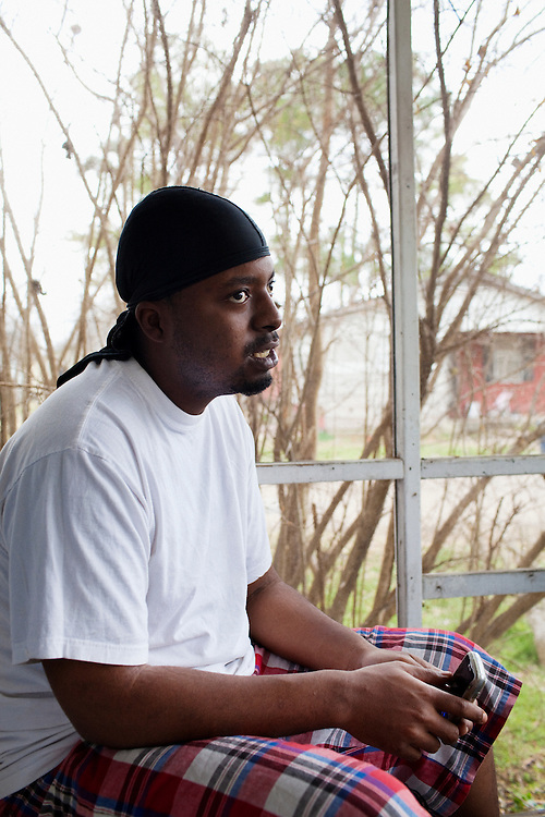 Jabari Wilson, 26, sits on the porch of the home he shares with his mother Ellen in the Baptist Town neighborhood of Greenwood, Mississippi on February 18, 2011.