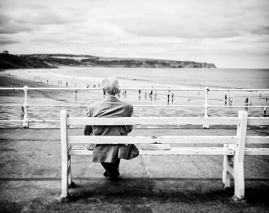 An old man sits gazing out to sea, on a white bench at a seaside resort.  Families can be seen on the beach beyond with cliffs in the distance