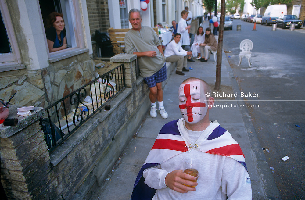 Sitting in chair outside his house in the East End of London, a young football fan waits for his painted face to dry. In the colours his favourite Tottenham Hotspur Football Club, he also wears a Union Jack cape. He sits with an outdoor party behind him in full swing that celebrates the 50th anniversary of VE (Victory in Europe) Day on 6th May 1995. In the week near the anniversary date of May 8, 1945, when the World War II Allies formally accepted the unconditional surrender of the armed forces of Germany and peace was announced to tumultuous crowds across European cities, the British still go out of their way to honour those sacrificed and the realisation that peace was once again achieved. Street parties now - as they did in 1945 - played a large part in the country's patriotic well-being.