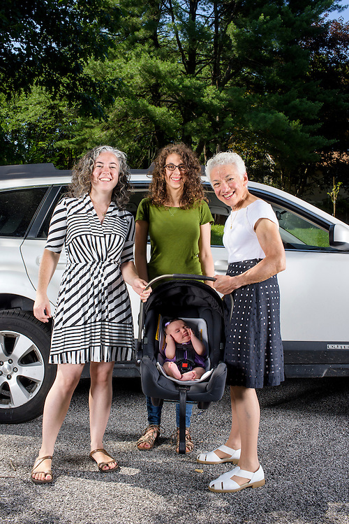 Pikesville, Maryland - June 25, 2015:  The Car Seat Ladies (L-R) Alisa Baer, 35, Emily Levine, 34, both from Manhattan, and Alisa's mother Deborah Baer, 67, from Pikesville, Maryland, hold Alisa's 7 week-old niece Leora Aghion in a Nuna Pipa infant car seat, ($300) at her sister's house in Pikesville, Maryland Thursday June 25th, 2015. <br />