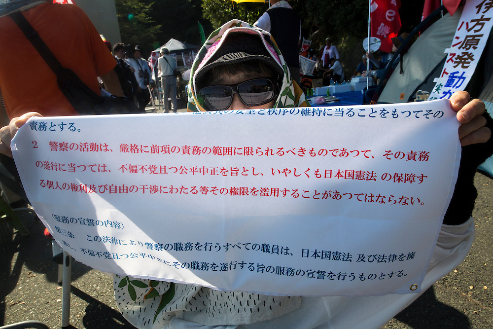 EHIME, JAPAN - AUGUST 12 : Anti-nuclear protester showing a banner that shows police law article 2 sec. 2 in front of Ikata Nuclear Power Plant to protest against the restarting of a nuclear reactor on August 12, 2016 in Ikata, Ehime prefecture, northwestern Shikoku, Japan. The Shikoku Electric Power Company restarted the plant's No.3 reactor at around 9 AM on Friday. It is the third plant to go online under new regulations issued after the Fukushima Daiichi nuclear disaster. (Photo by Richard Atrero de Guzman/NURPhoto)
