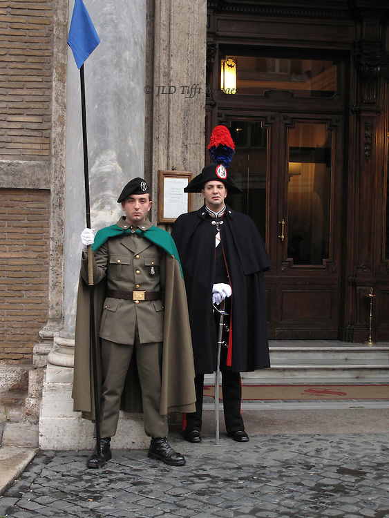 Two guards outside Roman Senate building, one Carabinieri wearing plumed hat, the other regular army, also in uniform and holding an upright staff.