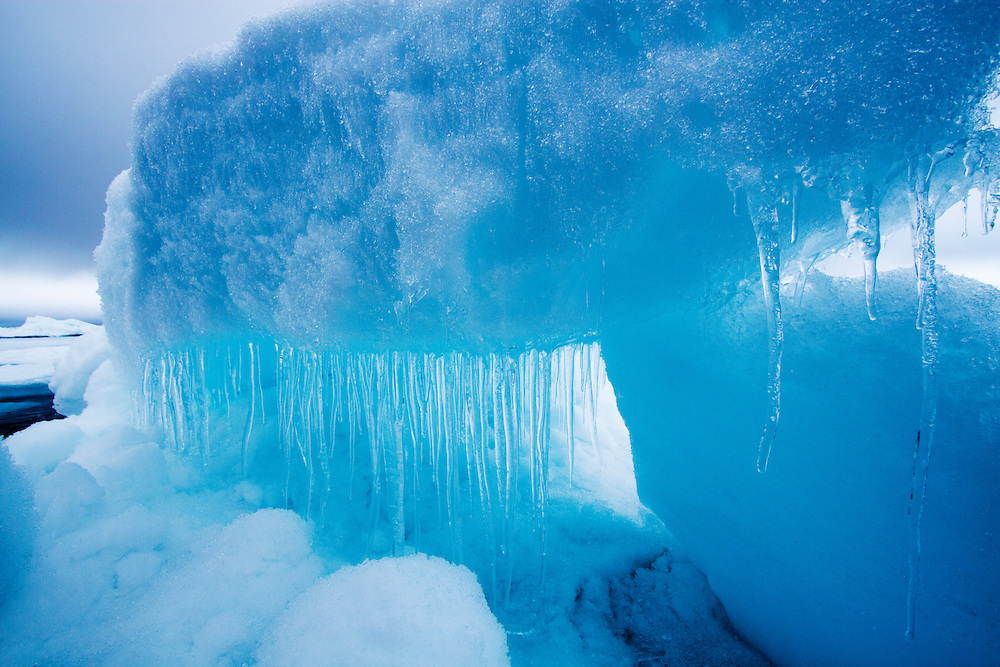 Norway, Svalbard, Icicles hang from melting sea ice in fog near Phippsøya (Phipps Island) amid fog-covered northern islands on summer morning