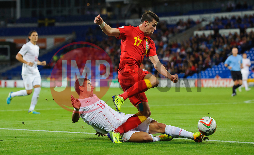 Gareth Bale of Wales (Real Madrid) is tackled by Aleksandar Kolarov of Serbia (Manchester City) during the second half of the match - Photo mandatory by-line: Rogan Thomson/JMP - Tel: Mobile: 07966 386802 10/09/2013 - SPORT - FOOTBALL - Cardiff City Stadium - Cardiff -  Wales V Serbia- World Cup Qualifier.