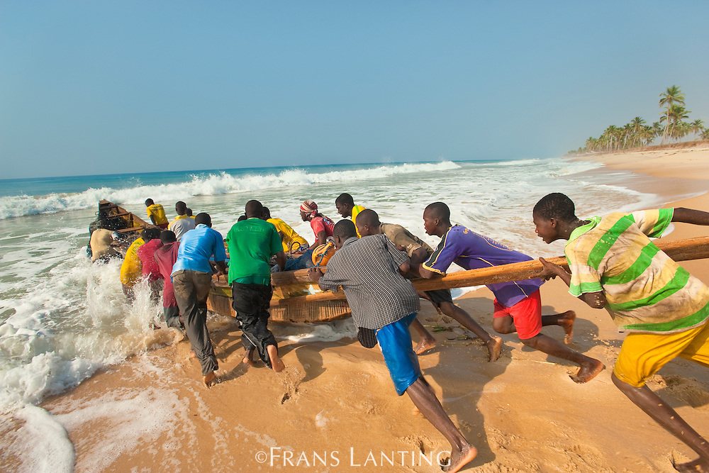 Fishmen pushing boat out through surf, Adah Foah, Ghana