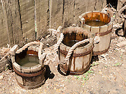 """Old style wood water buckets with rope handle. Jamestown Settlement, Virginia, USA. Jamestown Settlement, operated by the state's Jamestown-Yorktown Foundation, chronicles 1600s Virginia and the convergence of Powhatan Indian, European, and west central African cultures. Jamestown, the first permanent English settlement in the Americas, was founded as James Fort in 1607 within an area controlled by the Paspahegh tribe, which was part of the Powhatan Confederacy of tribes, Tsenacommacah, comprised of about 14,000 native people ruled by Wahunsonacock (sometimes called """"Powhatan""""). Created as part of the 350th anniversary celebration in 1957 as """"Jamestown Festival Park,"""" Jamestown Settlement is adjacent to the complementary """"Historic Jamestowne"""" museum (which is on Jamestown Island, is the actual historic and archaeological site where the first settlers lived, and is run by the National Park Service and Preservation Virginia)."""