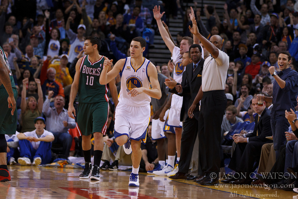 Mar 16, 2012; Oakland, CA, USA; Golden State Warriors guard Klay Thompson (11) celebrates after making a three point basket against the Milwaukee Bucks during the second quarter at Oracle Arena. Mandatory Credit: Jason O. Watson-US PRESSWIRE