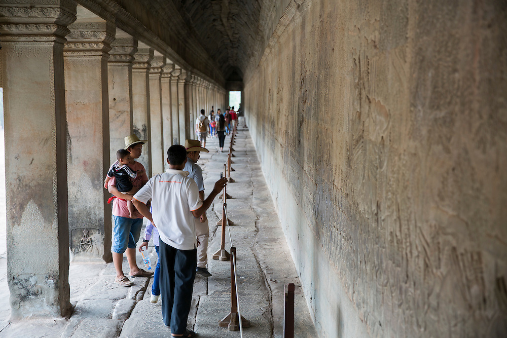 A tour guide gives a talk about the bas-relief friezes stone carving along the corridor walls within Angkor Wat temple, Siem Reap, Cambodia.  Angkor Wat is one of UNESCO's world heritage sites. It was built in the 12th century and covers 162 hectares.  It is Cambodia's main tourist attraction.  (photo by Andrew Aitchison / In pictures via Getty Images)