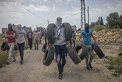 May 3, 2019 - Kafr Qaddum, Palestine - A Palestinian is seen holding tires during the demonstration in the village of Kafr Qaddum-West Bank on May 3, 2019..Palestinians clashed with the Israeli army during a demonstration in the village of Kafr Qaddum. Israeli soldiers shot rubber bullets and live ammunition. Seven people were injured during the demonstration..Palestinians march every Fridays and Saturdays in the village of Kafr Qaddum since 2011 due to the closure of one of their roads and land confiscation by the Israeli authorities. These decisions were made to expand the Israeli settlement of Kedumim. Through this road, Palestinians were able to reach the main city of Nablus in 15 minutes, now it takes more than 45 minutes. (Credit Image: © Bruno Thevenin/NurPhoto via ZUMA Press)