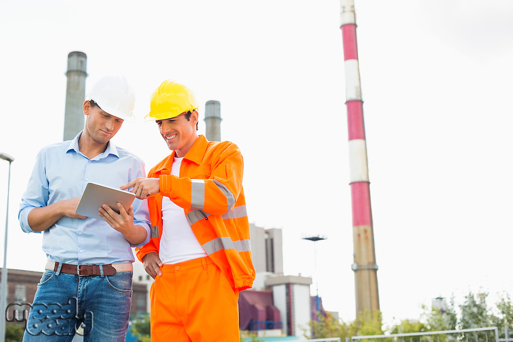 Two construction workers discussing over tablet PC at industry