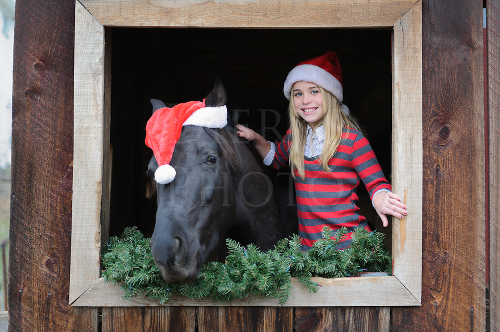Young girl and horse wearing Santa Christmas hats in open barn window.