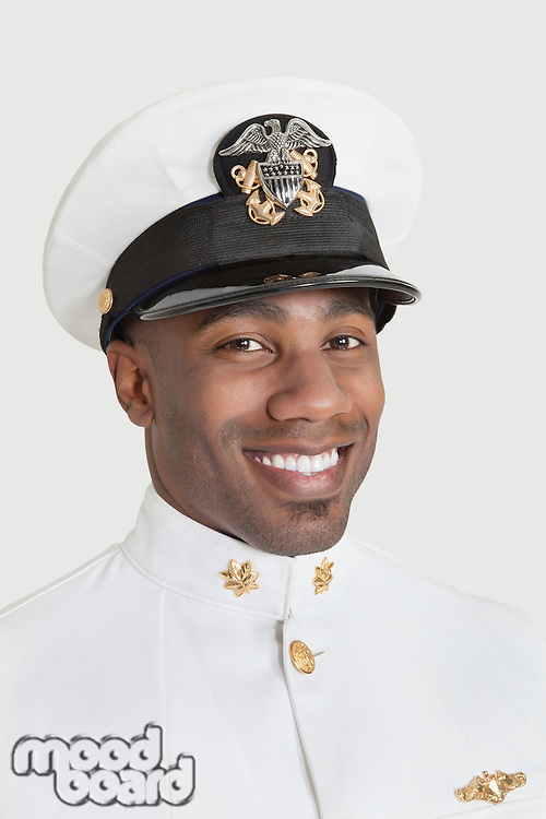 Portrait of a happy young African American US Navy officer over gray background