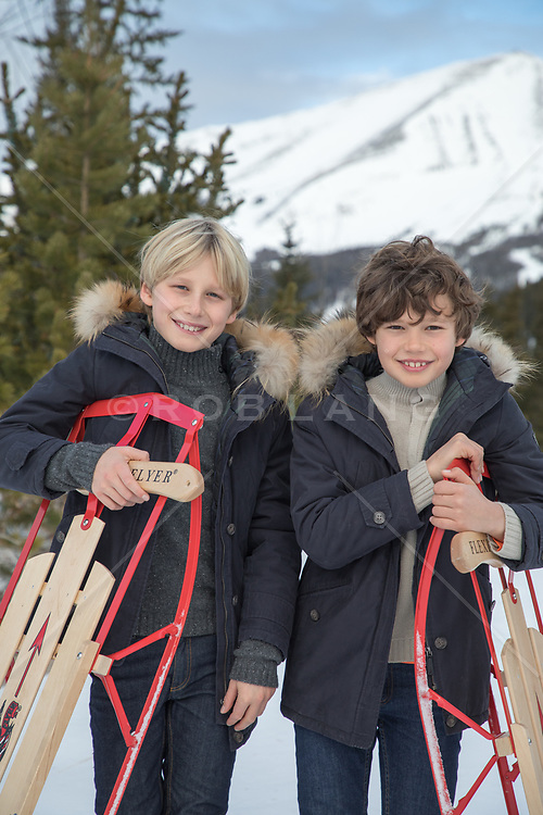 twin boys holding sleds by a ski mountain