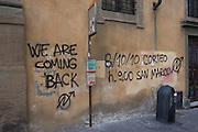 Political graffiti sprayed by aerosol on public building near Ponte Vecchio in Florence.